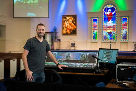 Regent University Chief Audio Engineer Justin Fugett stands at the helm of an Allen & Heath dLive S7000 control surface